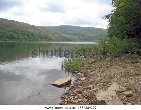 Pennsylvania waterway with trees rocks and cloud reflections