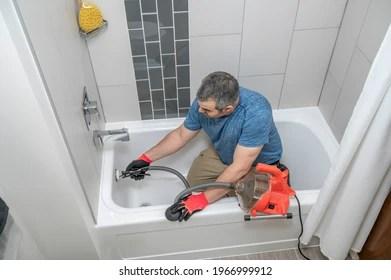 https www shutterstock com image photo plumber drain cleaning bathtub plumbers snake 1966999912
