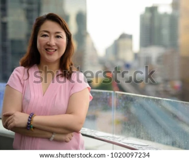 Portrait Of Mature Asian Woman Against View Of The City In Bangkok Thailand