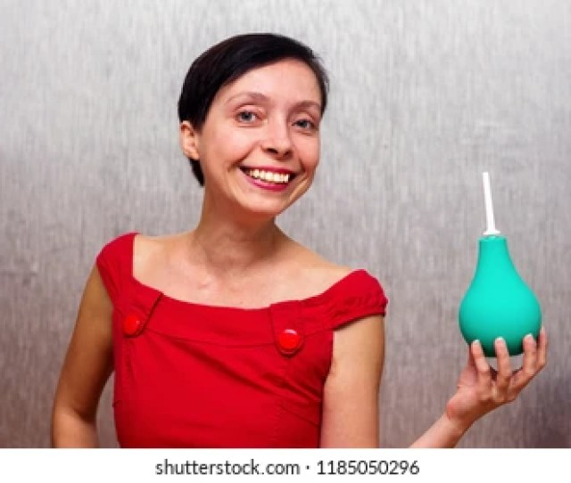 Smiling And Happy Woman Holding An Enema Isolated By Gray Background