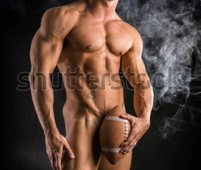 Totally Naked Male Bodybuilder Hiding Genitalia With American Football Ball Looking At Camera On