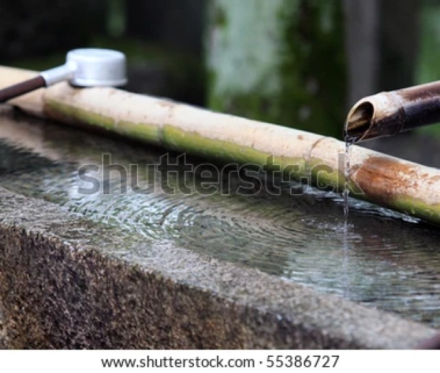 Traditional Japanese Bamboo Fountain Dripping Water With Ripples In A Basin