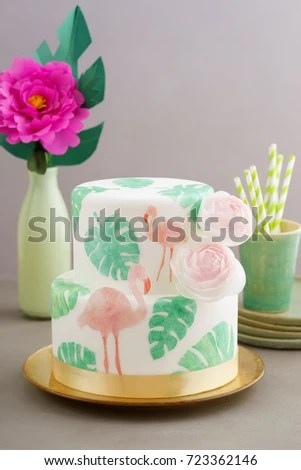 two tiered tropical wedding cake with fondant tropical wafer paper leaves and flamingos with ranunculus