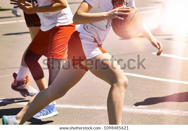 Las mujeres juegan al baloncesto. Grupo de chicas adolescentes felices con uniforme deportivo, jugando baloncesto al aire libre en la ciudad.
