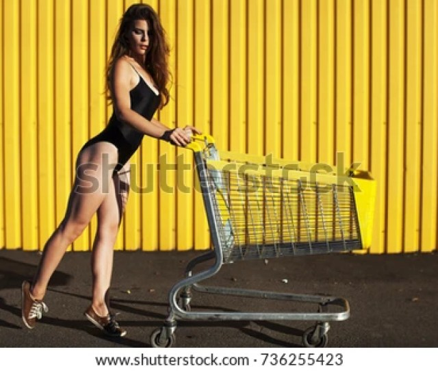 Wonderful Woman With Nice Ass In Black Swimsuit Posing Near Supermarket And Looking At Camera