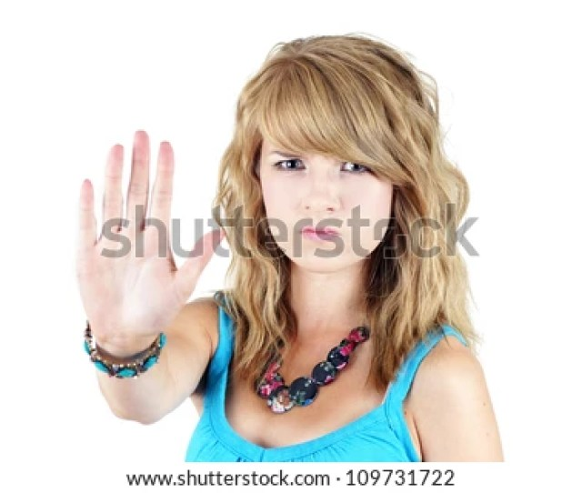 Young Blond Teenager Girl With Sad Or Angry Face Raising Her Hand To Say No Or