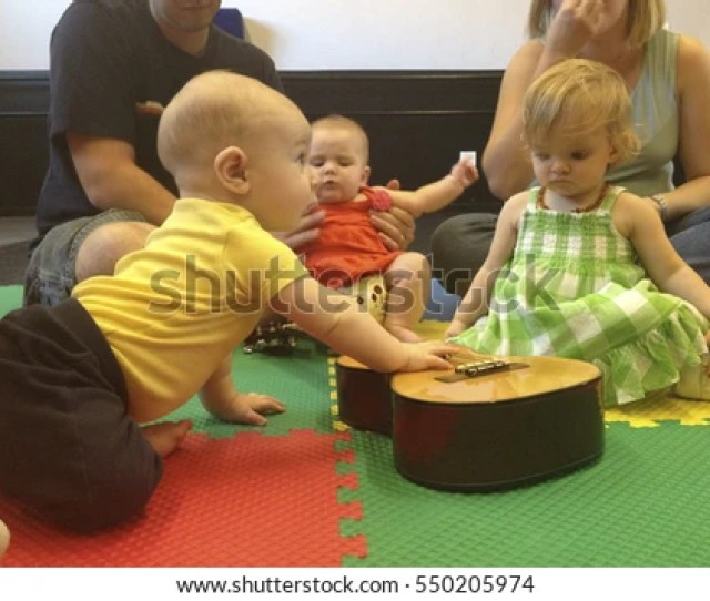 Young Children Are Playing With A Guitar In A Music Class For Toddlers As Parents Watch