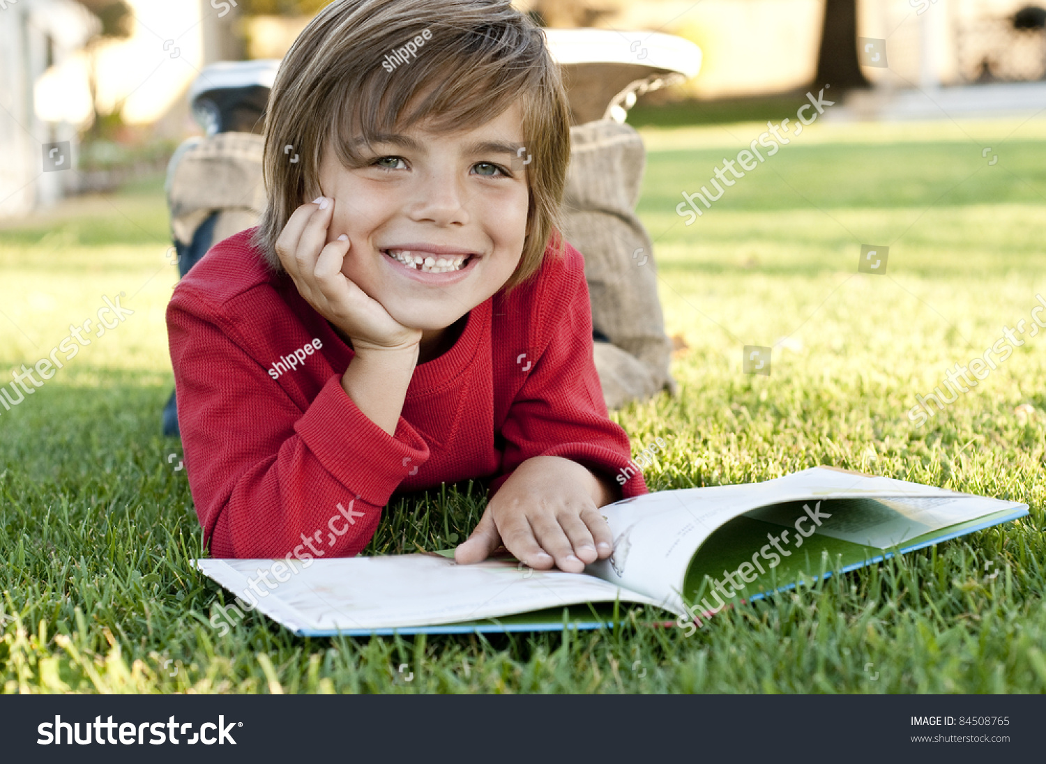 Very Cute 7 Year Old Boy Lying On The Grass Reading A Kids