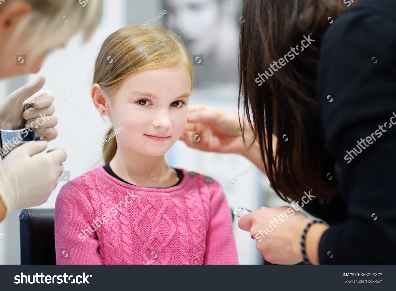 Adorable Little Girl Having Ear Piercing Stock Photo
