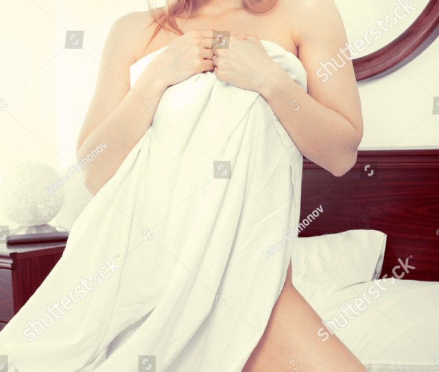 Cheerful Charming Woman Without Clothes Standing And Covering Herself With A Sheet In The Bedroom