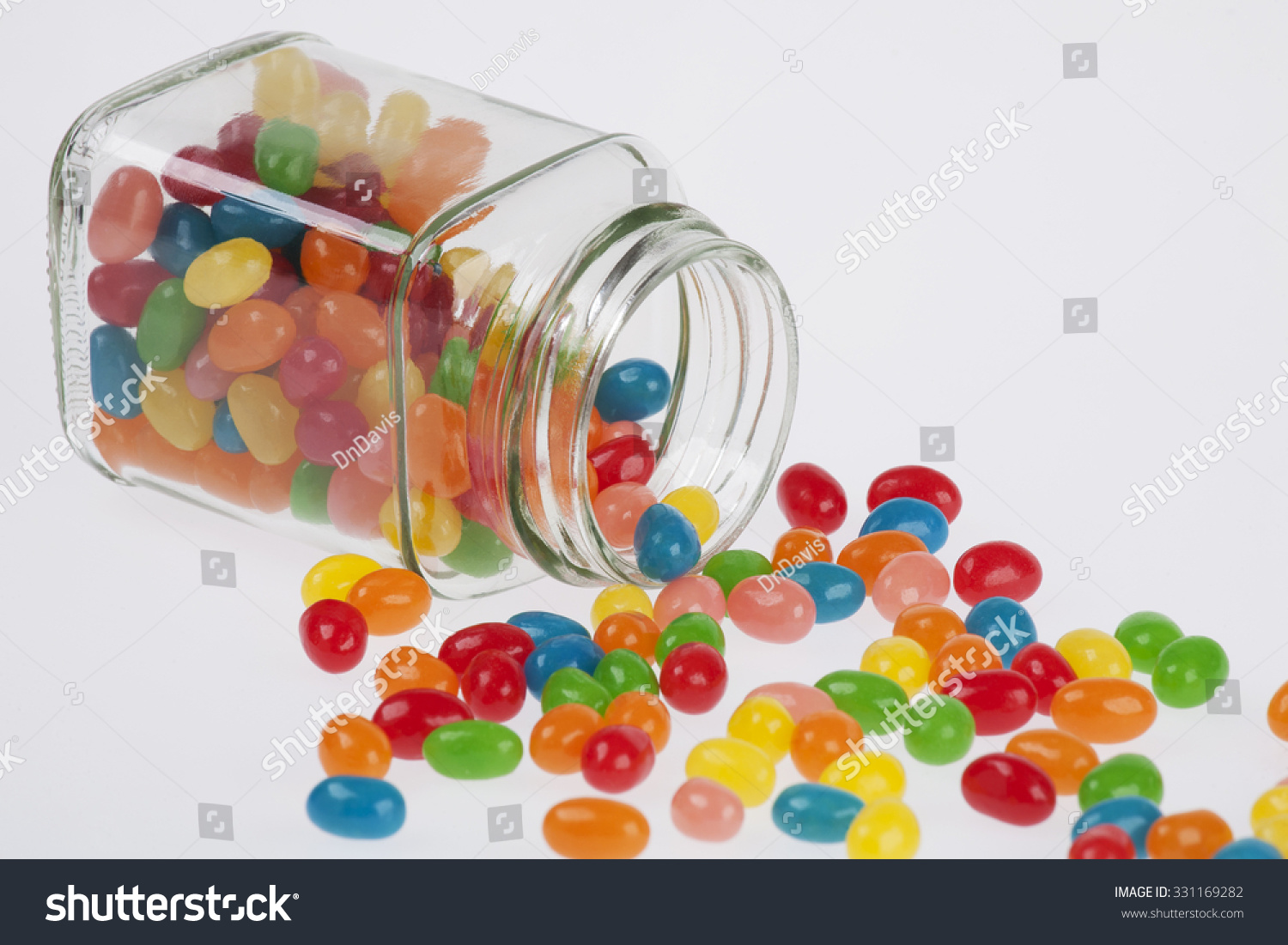 Close Up Of A Delicious Jelly Beans Candy Spilled From A Glass Jar Isolated On A White