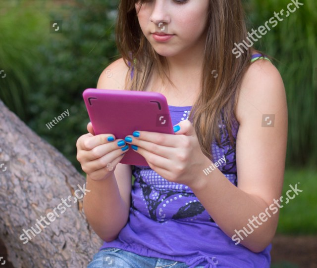 Cute Teen Girl Reading A Digital Book While Sitting On The Branch Of A Tree
