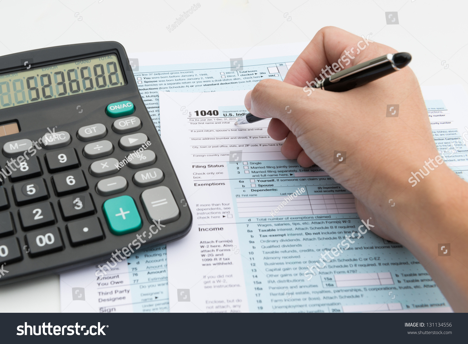 Filling Out Income Tax Forms Calculator Stock Photo
