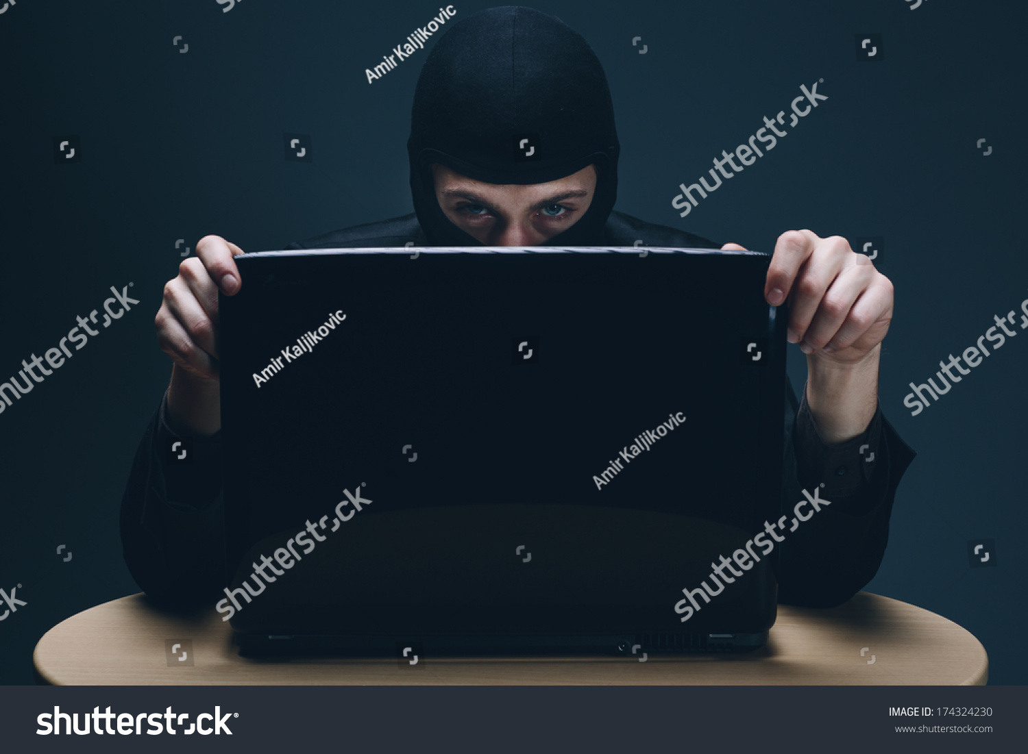 Furtive Masked Hacker Accessing Laptop Computer Stock Photo