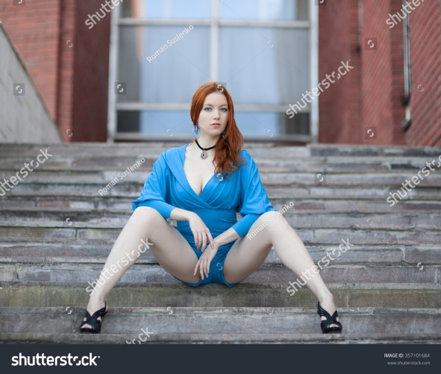 Red Haired Girl In A Turquoise Dress Sitting On The Stairs Legs Apart