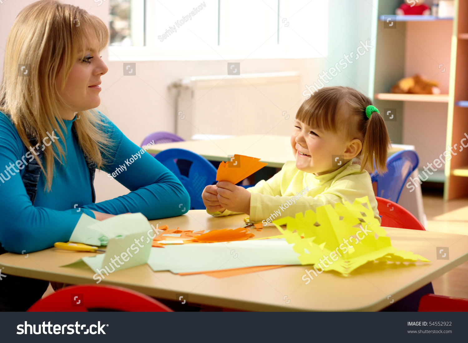 Teacher And Cute Little Girl Play With Color Paper In