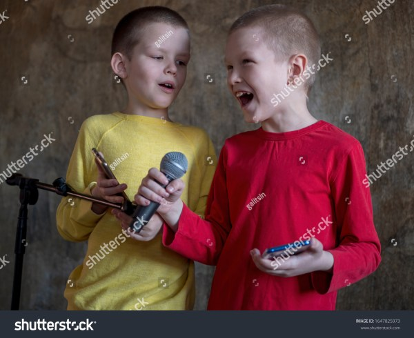 Swinging Two happy little boys received latest smartphone models as gift from their parents. children turned on music and sang karaoke in front of microphone on stand. Brothers are happy together, adore gadget