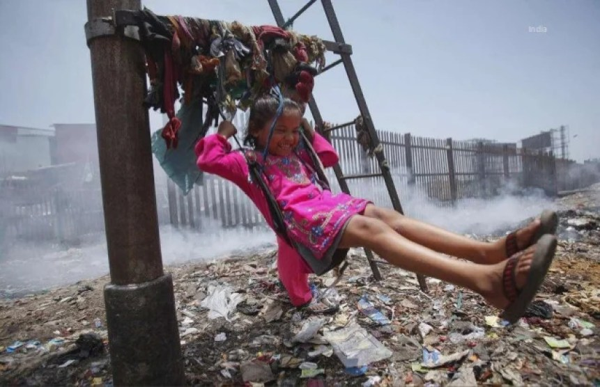 Girl playing on a swing made of clothing above a pile of rubbish