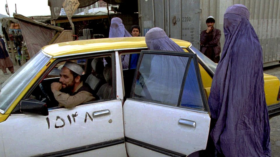 Afghanistan: Two women in light blue burqas get into the back of a white and yellow taxi on a street in Kabul