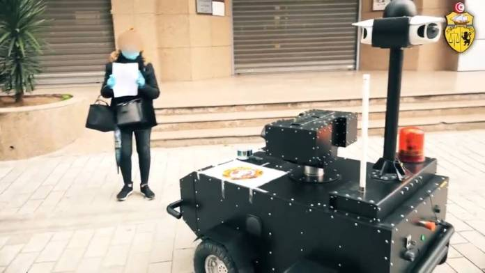Coronavirus in Tunisia: A woman shows her certificate of exit restrictions in Tunis to a police robot
