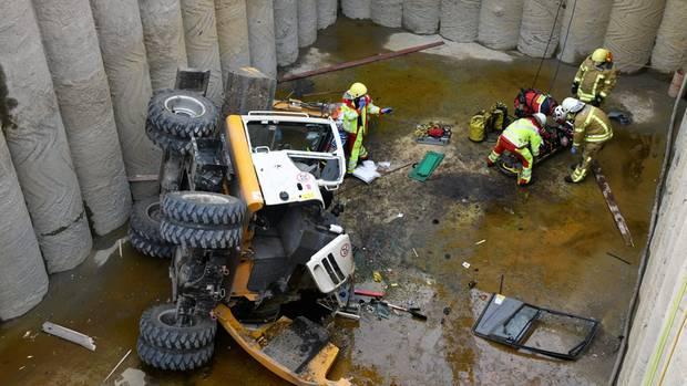 Paramedics and firefighters prepare an injured excavator driver for his recovery