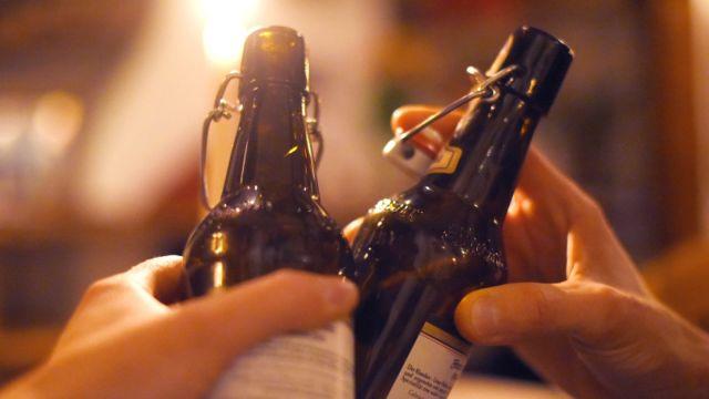 Zwei Hände stoßen mit Bierflaschen an