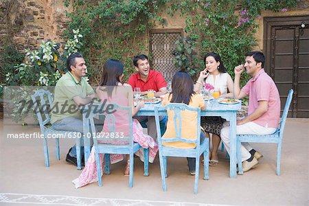 groupe de personnes assises autour d une table a manger photographie de stock masterfile premium libres de droits code 630 01872833