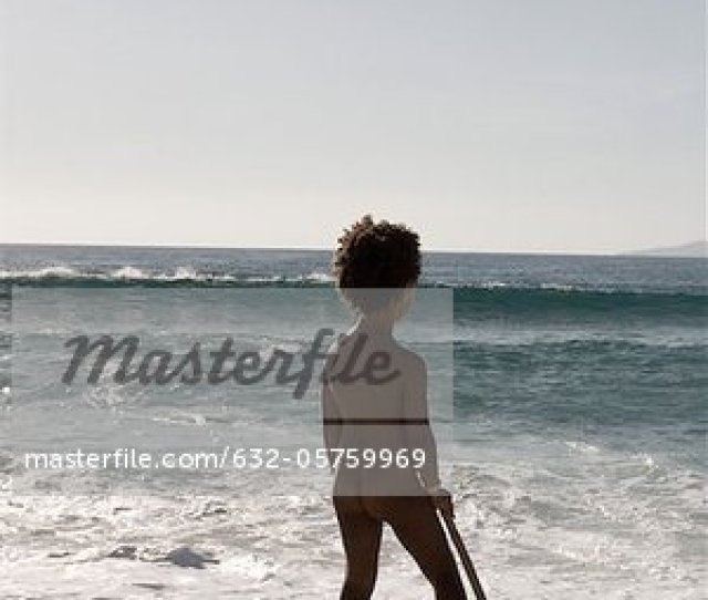 Little Girl Standing Naked At The Beach Rear View Stock Photo