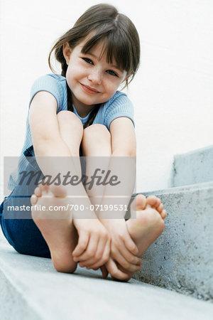 Portrait Of Girl Sitting Outdoors Holding Feet Stock Photo