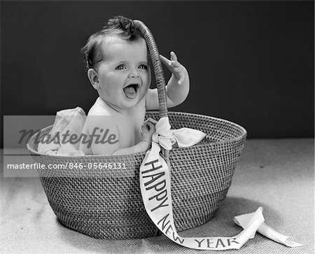 1940s BABY SITTING IN WICKER BASKET WITH HAPPY NEW YEAR BANNER     1940s BABY SITTING IN WICKER BASKET WITH HAPPY NEW YEAR BANNER STUDIO  INDOOR   Stock Photo