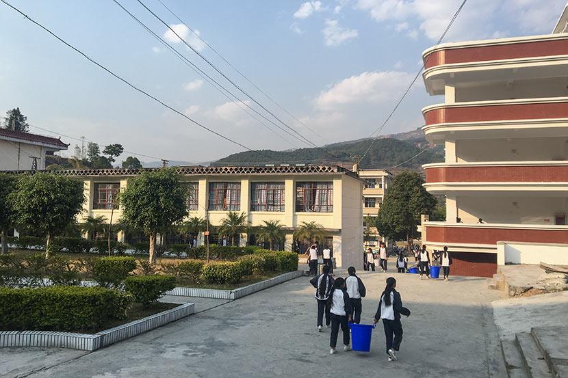 Students pick up trash after class at Nanjian No. 2 Middle School in Nanjian Yi Autonomous County, Yunnan province, March 22, 2018. Fan Yiying/Sixth Tone