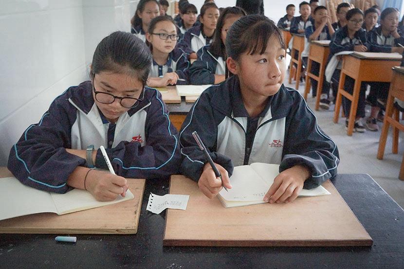 Students take notes during a career-sharing event at Nanjian No. 2 Middle School in Nanjian Yi Autonomous County, Yunnan province, March 22, 2018. Fan Yiying/Sixth Tone