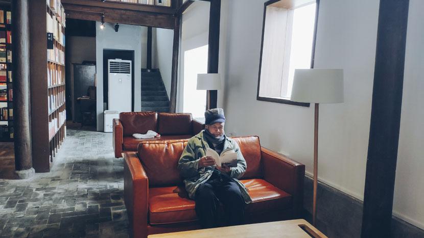 Bao Genyu reads a book in Chenjiapu Bookstore in Songyang County, Zhejiang province, Jan. 1, 2019. Fan Yiying/Sixth Tone