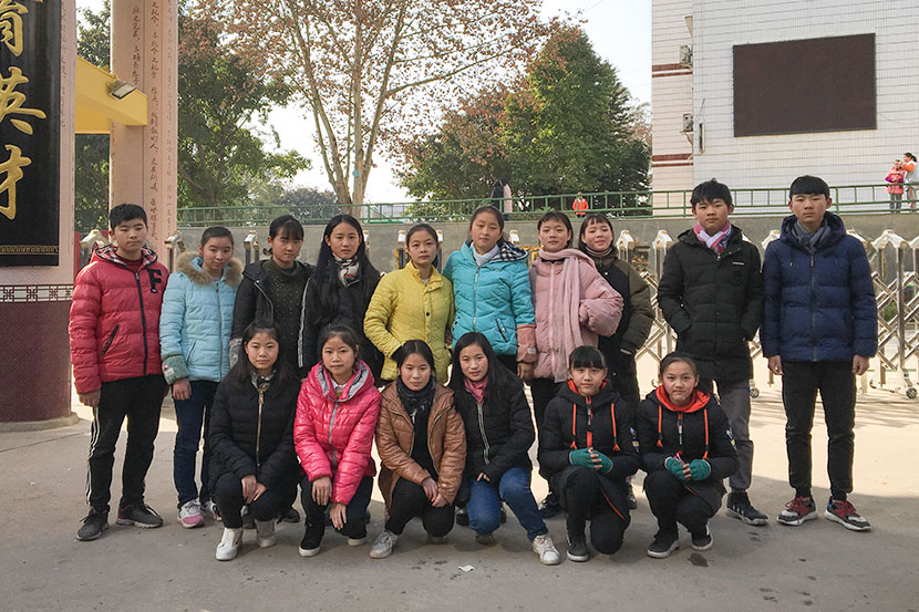 Eight sets of twins who attend Guxian Secondary School pose for a photo in front of the school's gate in Sichuan province, Jan. 9, 2018. Fan Yiying/Sixth Tone