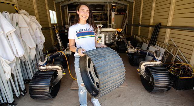 Isabel Rayas holds a spare mars rover wheel while posing in front of a rover parked in a garage