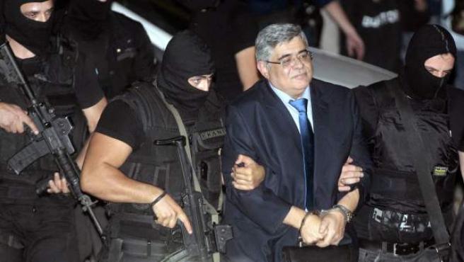 La Policía antiterrorista escolta a Nikos Michaloliakos, líder del partido neonazi griego Amanecer Dorado, a su llegada al tribunal de Atenas.