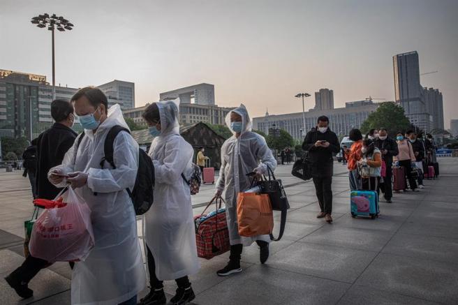 Pasajeros hacen cola frente a la estación de ferrocarril de Wuhan, en China, tras el levantamiento de algunas de las restricciones para viajar impuestas por la pandemia del coronavirus.