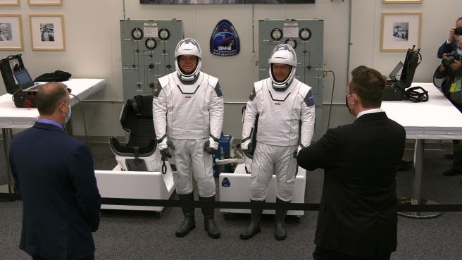 Los astronautas de la NASA Robert Behnken, a la izquierda, y Douglas Hurley hablan con el administrador de la NASA Jim Bridenstine, a la izquierda, y el CEO y diseñador jefe de SpaceX, Elon Musk, dentro de la sala de trajes en el Edificio Neil Armstrong de Operaciones y Pagos del Centro Espacial Kennedy.