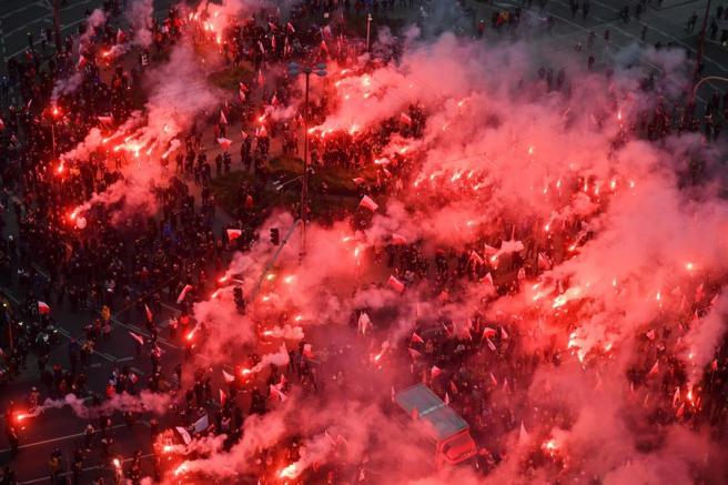 Polacos marchan con antorchas y banderas para celebrar el Día de la Independencia.