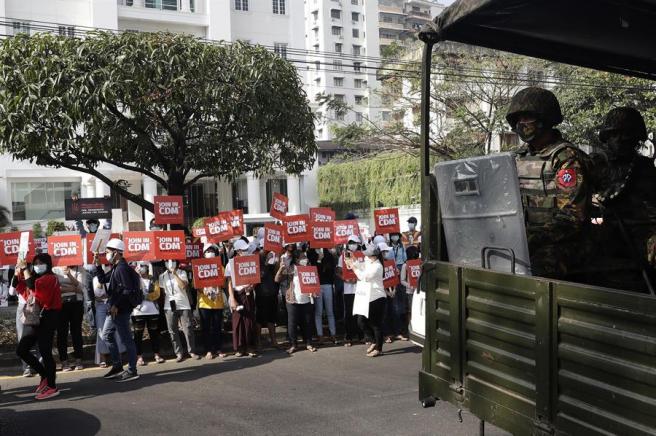 Manifestantes junto a un vehículo militar apoyan en Rangún, Birmania, el movimiento de desobediencia civil contra los militares que perpetraron el golpe de Estado en el país.