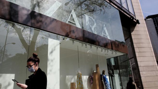 Una mujer con mascarilla pasa junto al escaparate de la tienda Zara de la Calle Princesa de Madrid