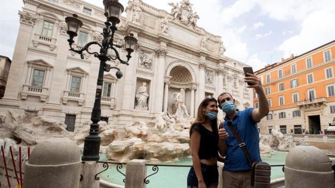 Una pareja se fotografía frente a la Fontana di Trevi, en Roma.