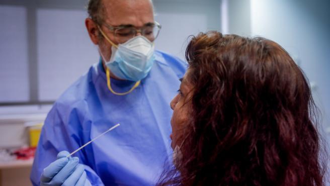Un trabajador sanitario realiza una prueba PCR a una de las personas que ha acudido a realizarse un test.