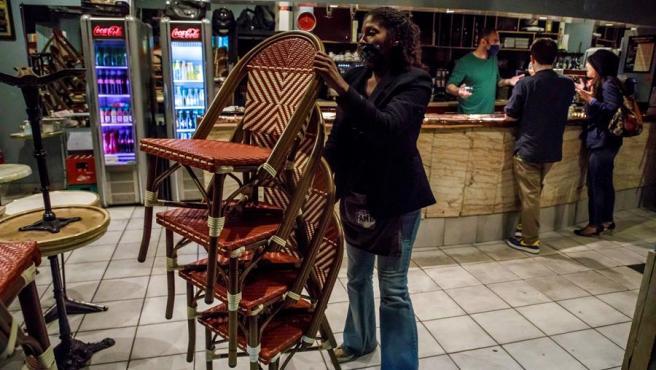 Una empleada recoge sillas en un bar en París, Francia, el primer día de la entrada en vigor de la prohibición de mantener los locales abiertos después de la 10 de la noche, por la pandemia del coronavirus.