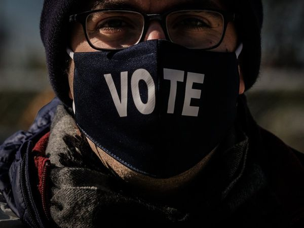 """Un votante con una máscara en la que se puede leer """"Vota"""" hace cola en un centro de votación en el Parque Nacional, en Washington, DC. Las de este martes serán unas elecciones complejas. El alto número de votos recibidos antes de la jornada electoral y las leyes de cada uno de los 50 Estados hacen impredecible definir el desarrollo de la noche."""