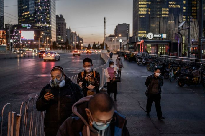 Varios ciudadanos, todos ellos con mascarilla, hacen cola para coger el autobús el pasado 20 de marzo en Pekín.