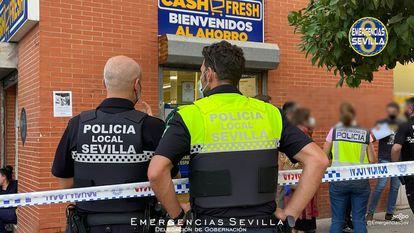 Varios agentes de la policía en las inmediaciones del supermercado de Sevilla en el que ha sido abatido un atracador este viernes por la tarde.