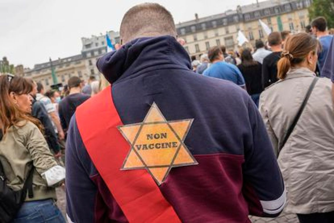"""A protester in Paris on July 17 with a Star of David on his back with the phrase """"Not vaccinated""""."""