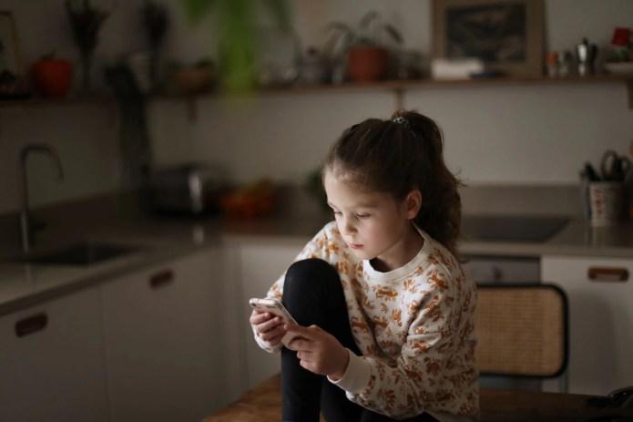 Una niña se entretiene con su teléfono móvil.