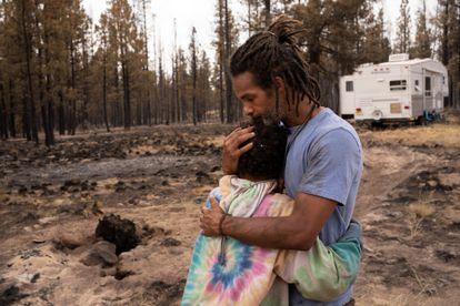 Un padre y un hijo se abrazan cerca de una caravana donada tras arder su casa en el incendio Bootleg cerca de Beatty, en Oregón, el 19 de julio.